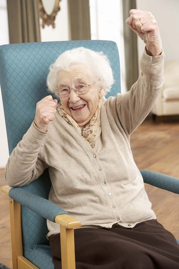Senior woman performing chair aerobics, adult day care center brooklyn nyc