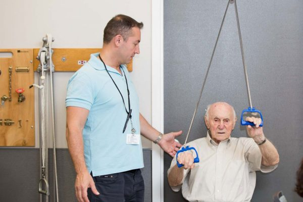 An old man suffering from frozen shoulders getting physical therapy at Fairview Adult Day Care Center Brooklyn, NY