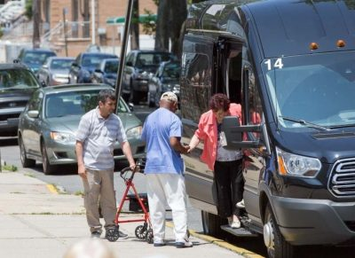 Fairview Adult Day Care staff helping elderly with transportation