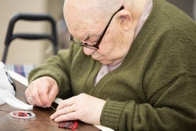 Senior man sewing to keep his brain healthy and to prevent cognitive decline