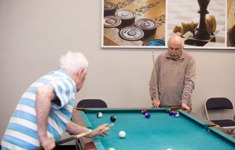 Elderly playing snooker for entertainment in russian-speaking elderly care