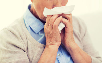 Sick senior woman suffering from cold and flu blowing nose to paper napkin