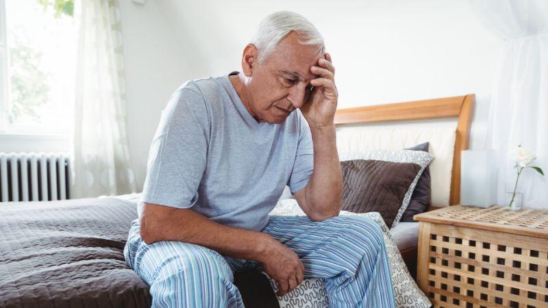 Stressed elderly man sitting on bed
