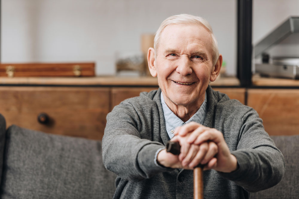 Cheerful old man suffering from loss of balance sitting on sofa smiling and holding walking cane