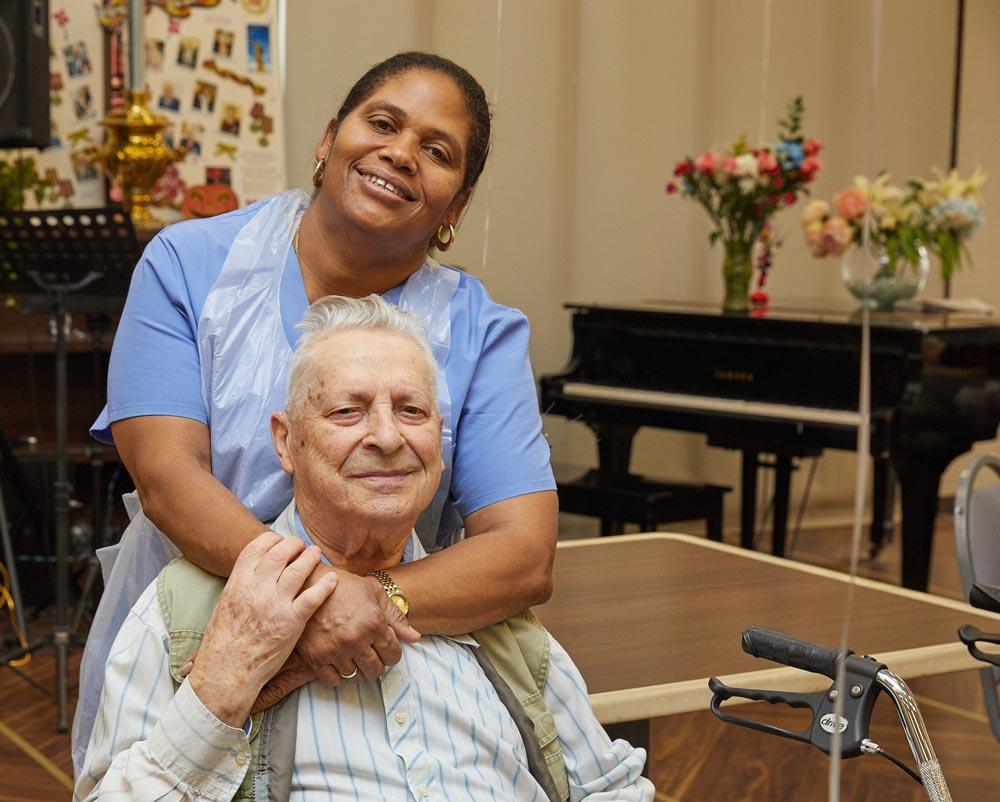 Black recreation nurse putting smile on an elderly man in order to boost emotional health