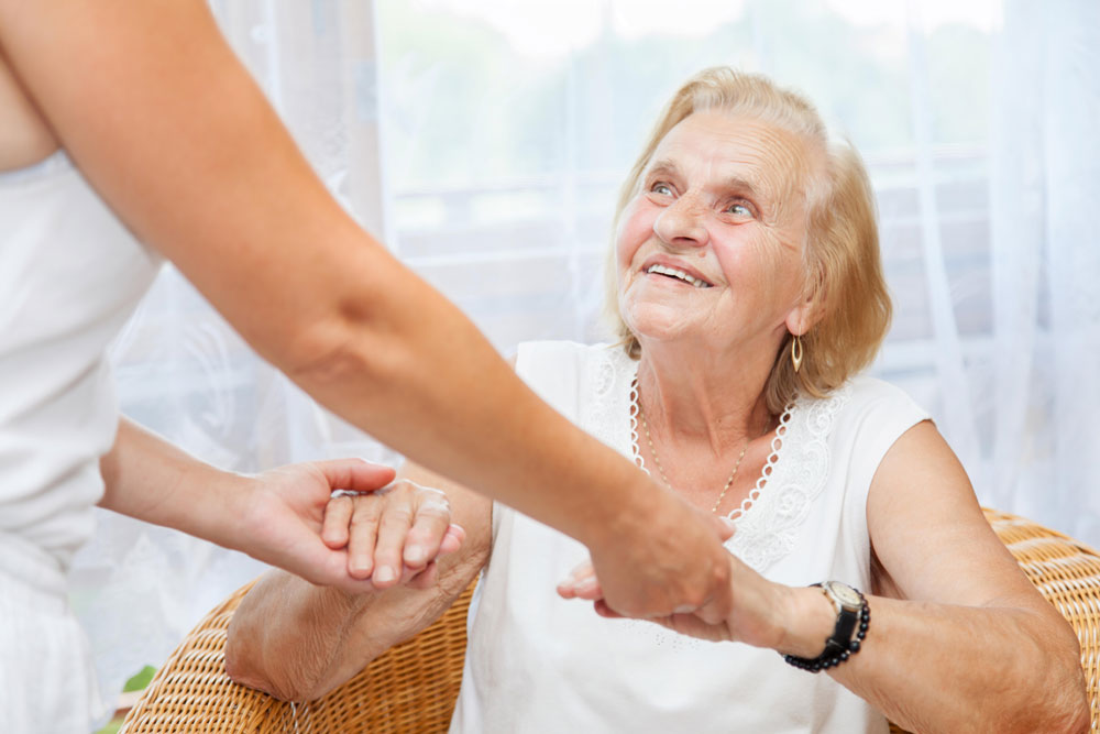 Nurse providing care for elderly woman with happy emotions