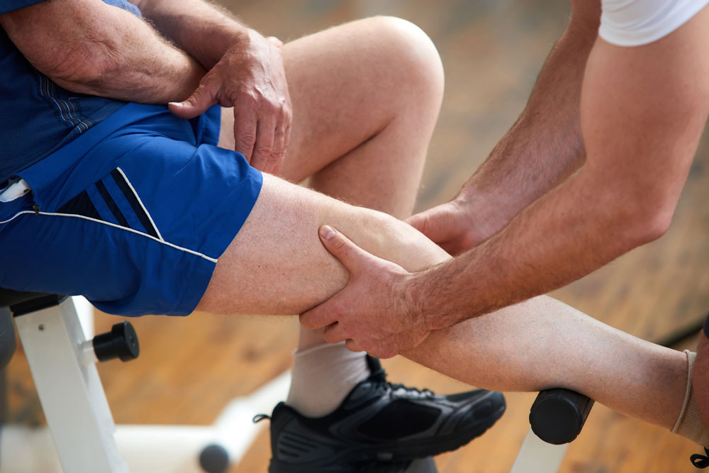 Physical therapist helping elderly with arthritis exercises suffering from joint pain