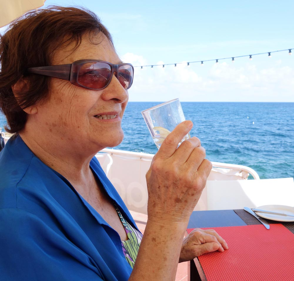 Elderly woman drinking water from glass to avoid heat exhaustion