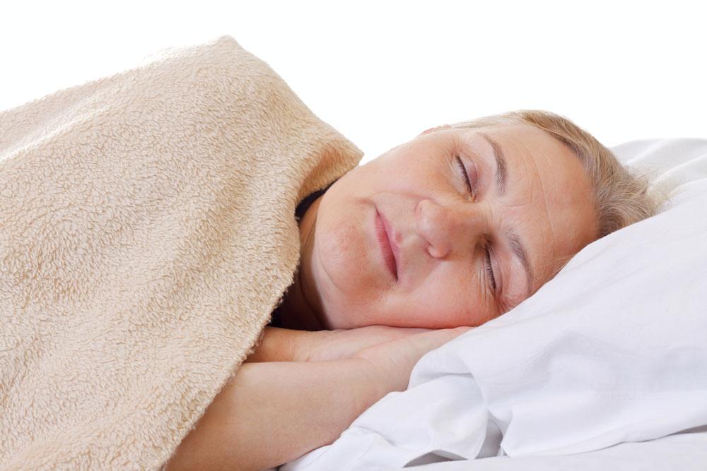 Elderly woman sleeping suffering from sleep apnea