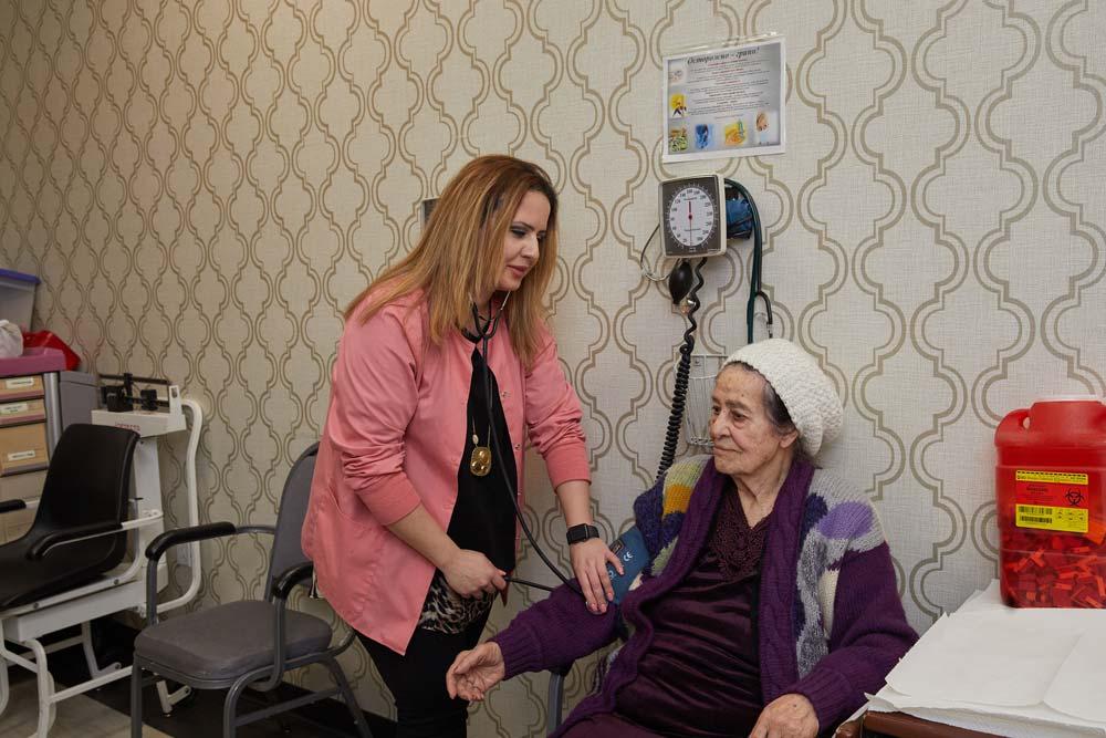 Nurse checking blood pressure of an elderly woman as a part of cardiac rehab