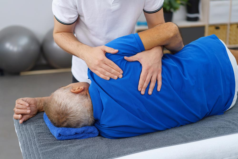 Physiotherapy providing Geriatric physical therapy to an elderly man