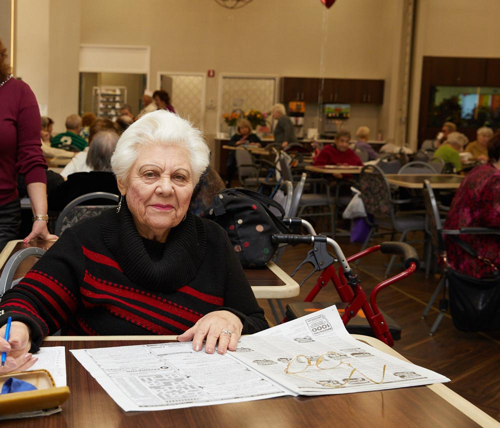 Elderly woman solving puzzles as a part of cognitive behavioral therapy