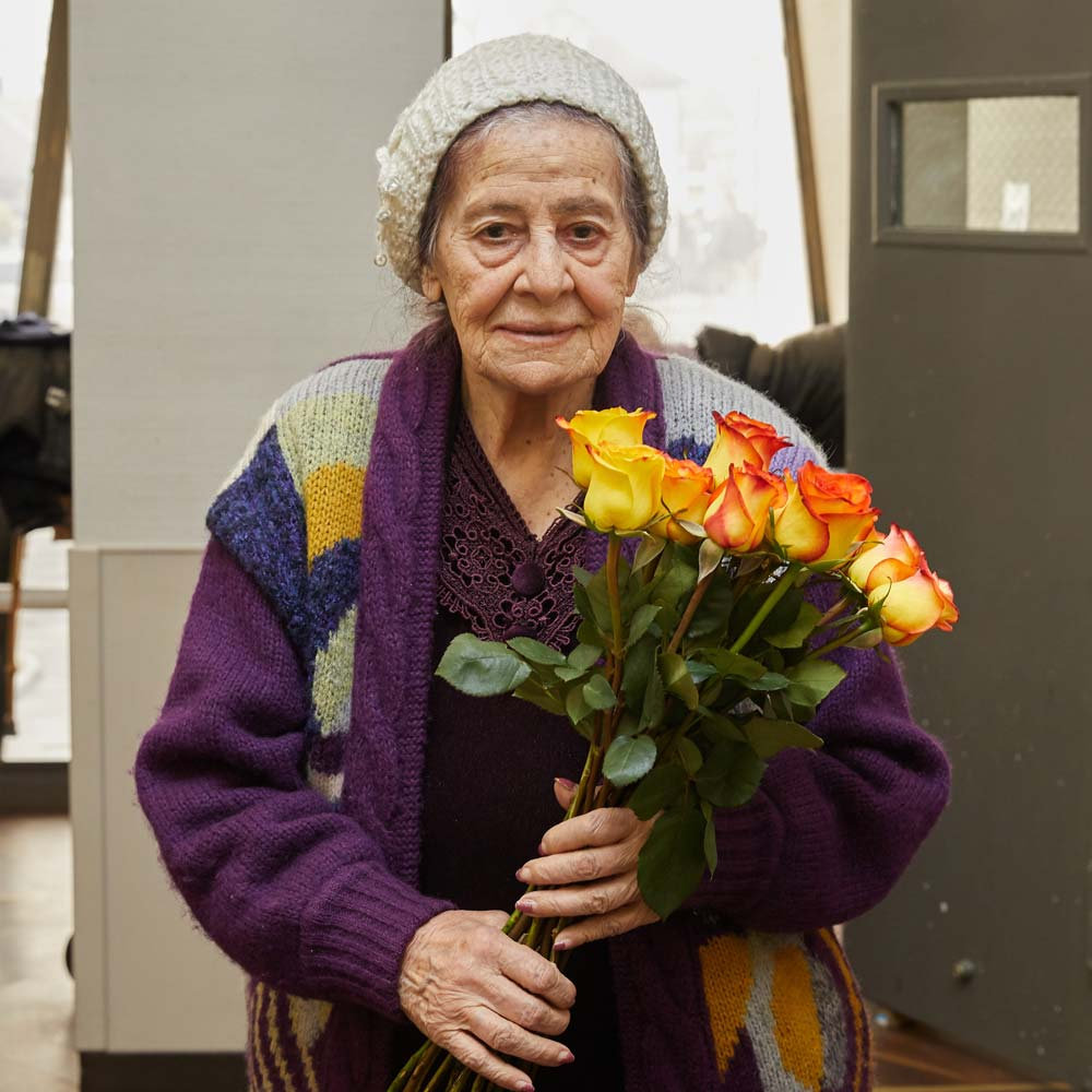 Elderly woman with depression holding bouquet