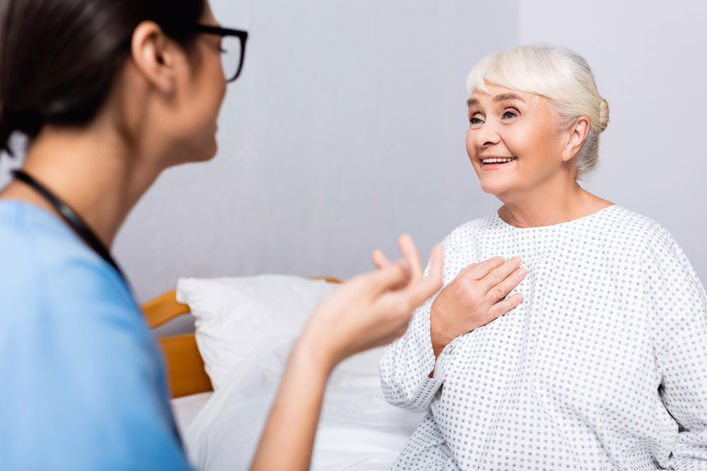 Elderly woman suffering from excess mucus touching chest while talking to the nurse